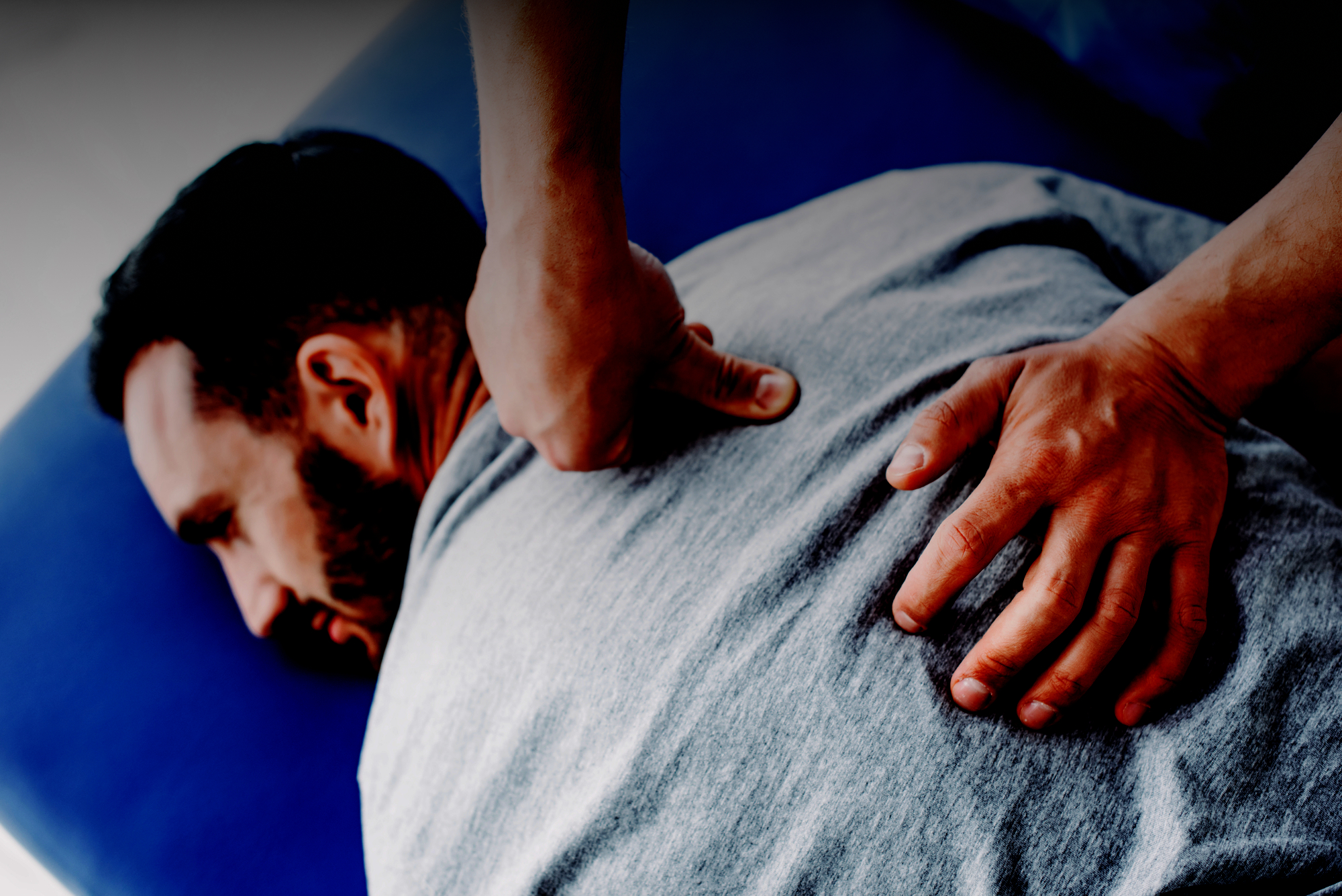 Man receiving back massage treatment on osteopath mat