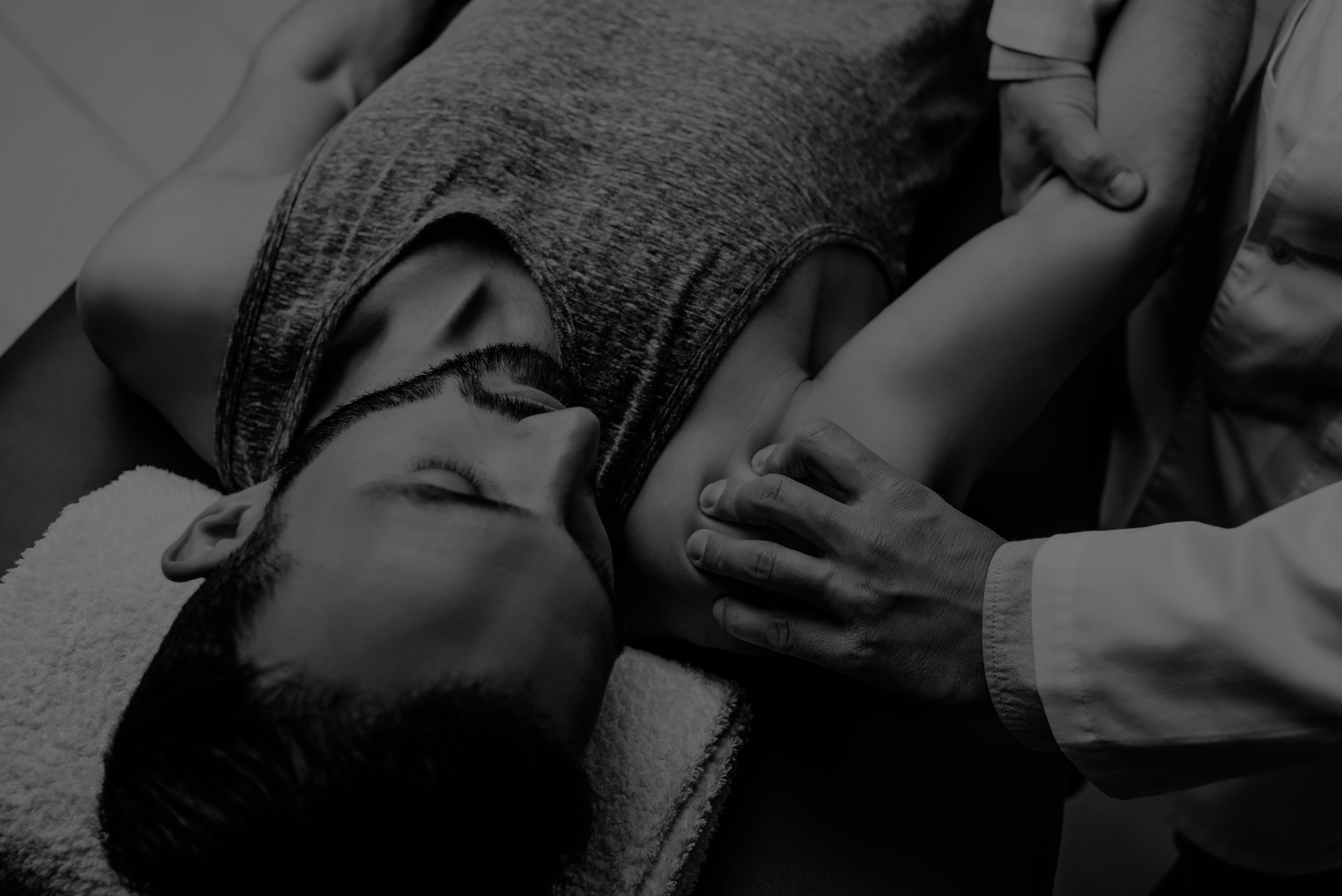 Black and white image of man receiving a should and elbow joint press with osteopath hands