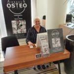 Correct Osteo Clinic female receptionist smiling at stall and ready to help