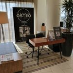 Correct Osteo Clinic stall inside building with sign, leaflets and desk set-up for the public to visit and express interest
